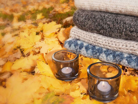 Yellow autumn leaves with candles, warm cozy sweaters autumn clothes Stockfoto - 131442050