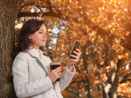 Beautiful woman drinking coffee outdoor and chatting on smartphone Stockfoto