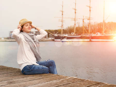 Woman in seaport relaxing with yachts on background. Stockfoto
