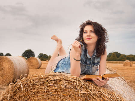 Beautiful Woman Reading book on a haystack, nature background Stockfoto - 131440562