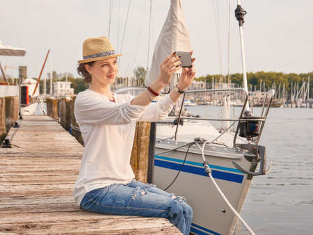 Woman in seaport making selfie with yachts on background. Stockfoto - 131439448