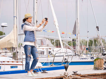 Woman in seaport making photo with yachts on background.