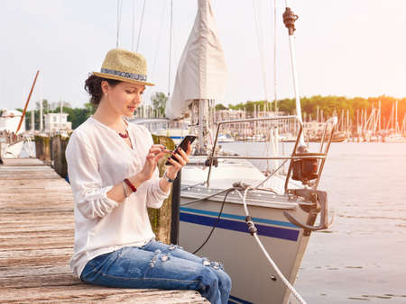 Woman in seaport chatting on smartphone with yachts on background.