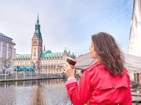 Young woman drinking coffee and walking outdoor in Hamburg city hall square, Germany.