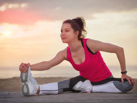 Beautiful fitness woman in sport clothes on a wooden pier. Sea and sunset sky background.
