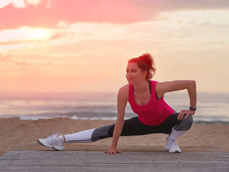 Beautiful woman doing yoga fitness exercise in sport clothes on a wooden pier.