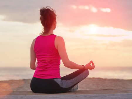Beautiful woman practicing yoga on a wooden pier. Sea and sunset sky background. Stockfoto