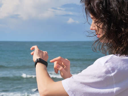 Woman looking at heart rate monitor watch outside jogging on beach.