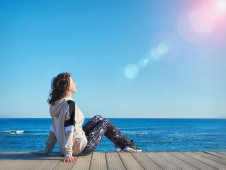 Woman on a wooden pier. Beach background. Yoga, sport, vacation and freedom concept.