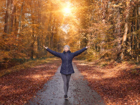 Freedom ideas concept, woman with raised hands up in forest Stockfoto