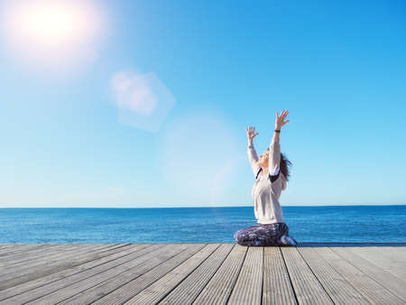 Woman with raised hands up to the sun. Freedom concept.