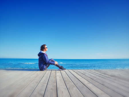 Woman on a wooden pier. Sea and sky background. Stockfoto