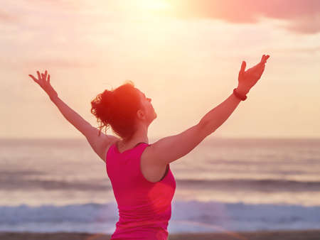 Beautiful fitness woman raised hands up to the sun. Yoga, sport and freedom concept.