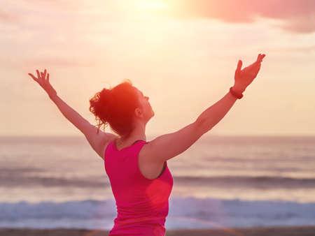 Mujer hermosa fitness levantó las manos hasta el sol. Concepto de yoga, deporte y libertad.