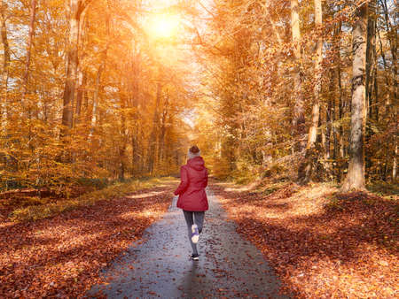 Woman running and training in fall nature Stockfoto