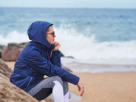 Portrait of a beautiful woman with a hood on a cloudy day at the beach Stockfoto