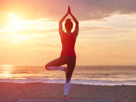 Hermosa practicando yoga en la playa. Fondo del cielo del mar y del atardecer. Concepto de yoga. Foto de archivo
