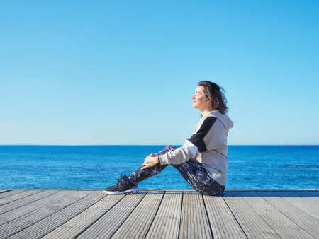 Woman on a wooden pier. Yoga, sport, vacation and freedom concept. Stockfoto