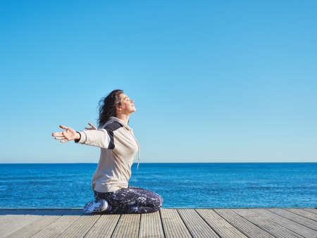 Woman on a wooden pier. Yoga, sport, traveling and freedom concept.