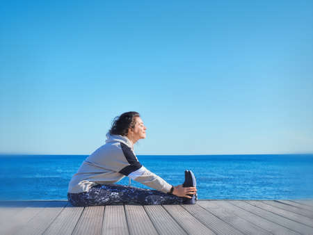 Woman making sport on a wooden pier. Sea and sky background. t. Stockfoto - 135033235