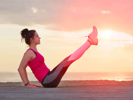 Beautiful woman doing yoga fitness exercise in sport clothes on a wooden pier. Sea and sunset sky background. Stockfoto - 135033413