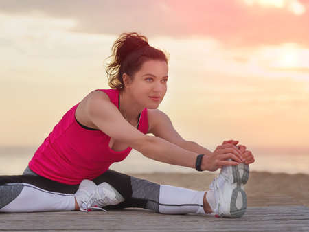 Beautiful woman doing fitness exercise and stretching her leg on a wooden pier