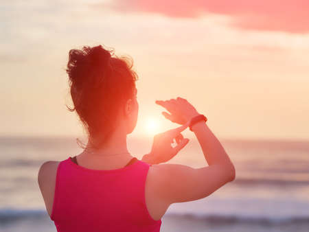Woman looking at heart rate monitor watch outside jogging on beach. Fitness, training outdoors