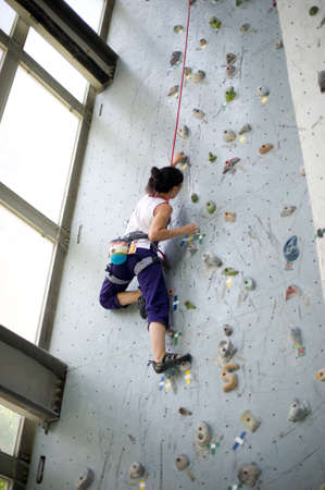 climbing wall: A girl wearing harness and belaying rope and climbing on a very high rock climbing wall