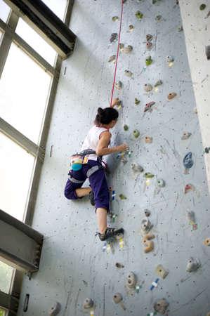 stijger: Een meisje met harnas en touw zekeren en klimmen op een zeer hoge rots klimwand Stockfoto
