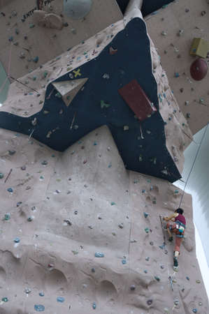 A girl wearing harness and belaying rope and climbing on a very high rock climbing wall
