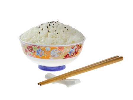Rice with some sesames on a ceramic bowl, chopsticks on the side. Isolated background. photo