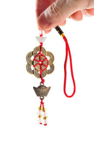 lucky charm: Hand held ancient Chinese coins connected by red strings and knots and decorated with small jades  Stock Photo