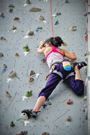escalada: Asian girl wearing harness and belaying rope, climbing on a very high rock climbing wall