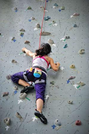 登る: アジアガール ビレイ ロープとハーネスを着て、非常に高いロック クライミングの壁を登る