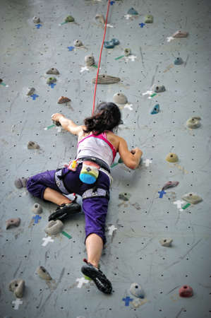 climber: Asian girl wearing harness and belaying rope, climbing on a very high rock climbing wall