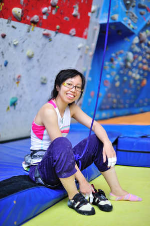 Asian girl wearing harness and belaying rope, ready to do rock climbing. photo