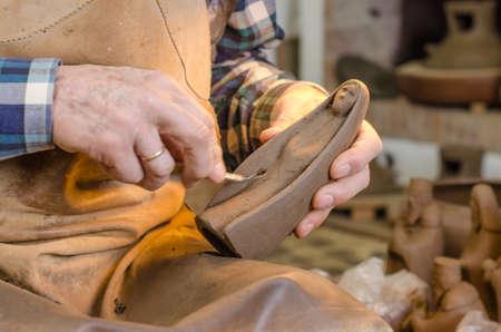 alfarero: Viejas manos de un alfarero que conforman una figura de arcilla