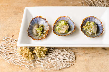 adhere: Limpets are marine mollusk with a conical shell, which adhere strongly to the rocks. They are a typical snack of the Canary Islands, especially roasted with a vinaigrette of olive oil, garlic, oregano, vinegar and salt.