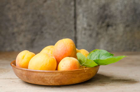 abundant: Beautiful wooden bowl full of ripe apricots with a rustic background.