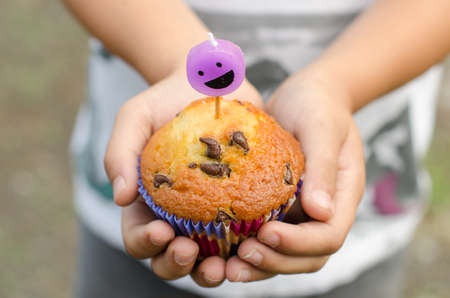 birthday food: Homemade chocolate chip cupcake and candle smiling in the hands of a child.