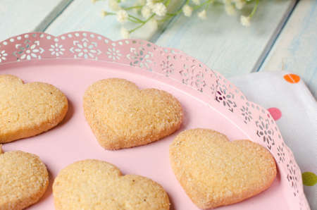 aniversary: Pink tray with butter and sugar cookies. Aged blue wooden background.