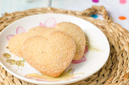 aniversary: Plate with three shortbread, heart-shaped, on a wicker mat.