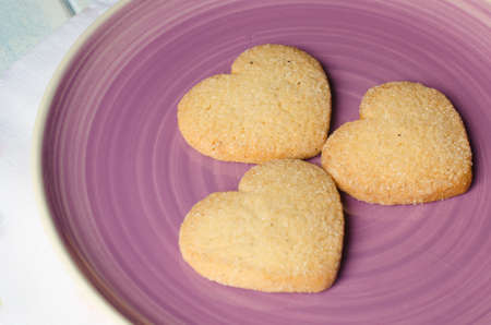 aniversary: Purple plate with three shortbread, heart-shaped, (butter cookies with sugar)