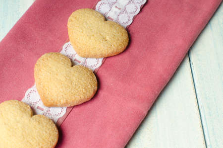 shortbread: Three shortbread, heart-shaped, on  pink and white clothes. Stock Photo