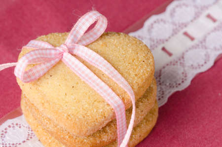 aniversary: Three shortbread, heart-shaped, on  pink and white clothes. Stock Photo