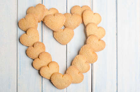 aniversary: Big heart made with shortbread, aged blue wooden background. Stock Photo
