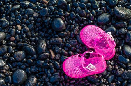 shingle beach: Pink water shoes on shingle beach. Stock Photo