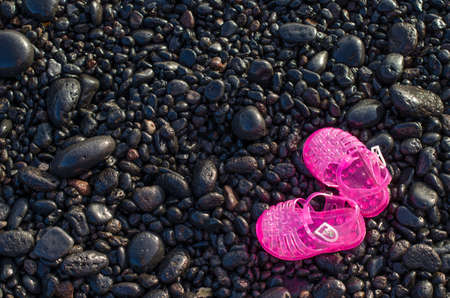 shingle: Pink water shoes on shingle beach. Stock Photo
