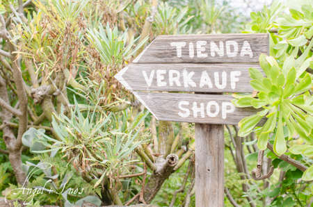 indicative: Wooden sign indicative shop, nature background. (Spanish, German, English) Stock Photo