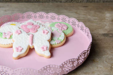 Freshly Baked Spring Flower Gourmet Cookies in a pink tray, on wooden table